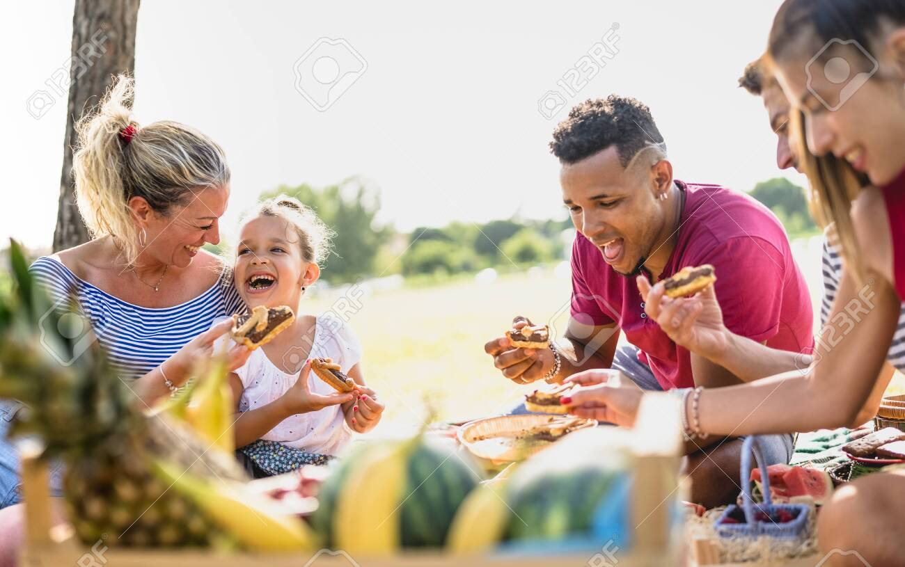 Cropped view of happy multiracial families having fun with kids at pic nic barbecue party - Multiethnic love concept with mixed race people eating with children at public park - Warm vivid filter - 140613936