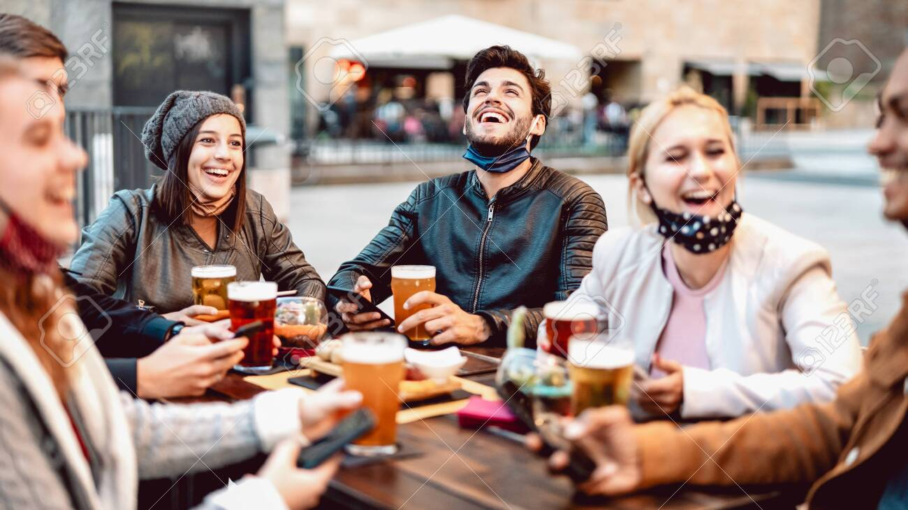 Young friends drinking beer wearing face mask - New normal lifestyle concept with people having fun together talking on happy hour at outside brewery bar - Bright warm filter with focus on central guy - 158045768