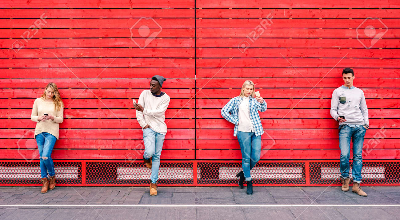 Multicultural friends group using smartphone by red wooden background - Technology and urban lifestyle concept with millenial people sharing content online with modern mobile phones - Vivid filter - 158431852