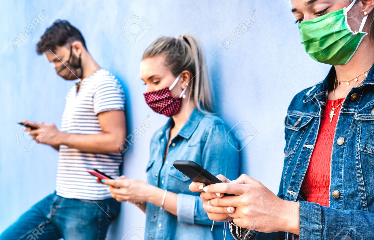 Milenial friends using mobile phone covered by face mask - Young people sharing content on cellphone - New normal concept about always connected teenager - Vivid azure filter with focus on right hands - 164791031