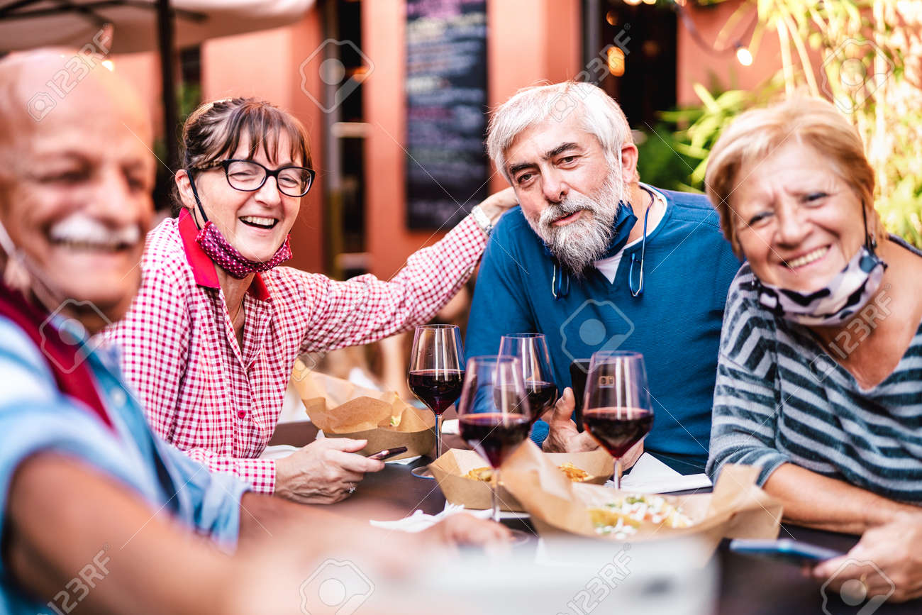 Happy senior friends taking selfie at restaurant with open face mask - Retired people having fun together at winebar after lockdown reopening - Positive elderly life style concept on vivid warm filter - 165216055