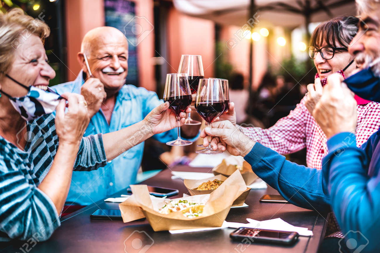 Senior people toasting wine at restaurant bar wearing open face masks - New normal life style concept with happy mature friends having fun together at garden party - Vivid filter with focus on glasses - 165216057