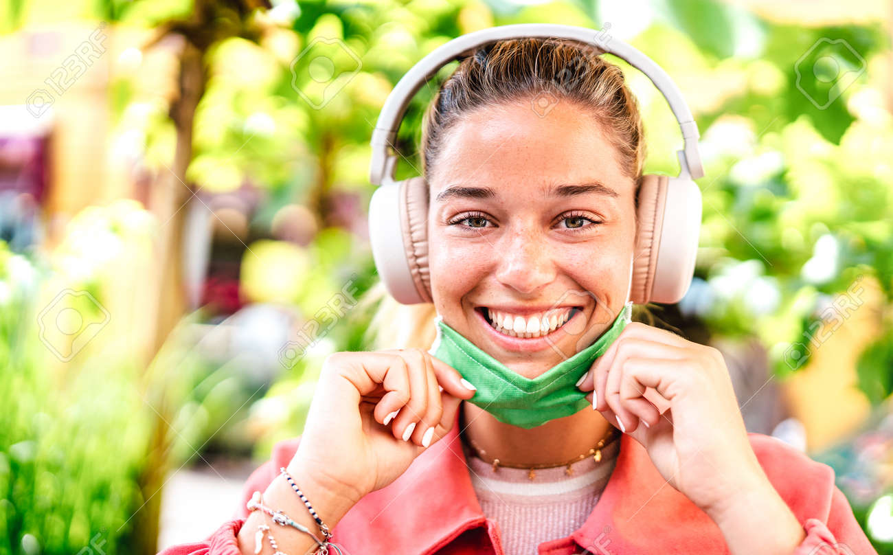 Young woman smiling looking at camera with open facial mask and headphones - New normal lifestyle concept with millenial girl having fun outdoors after lockdown reopening - Warm bright filter - 165845808