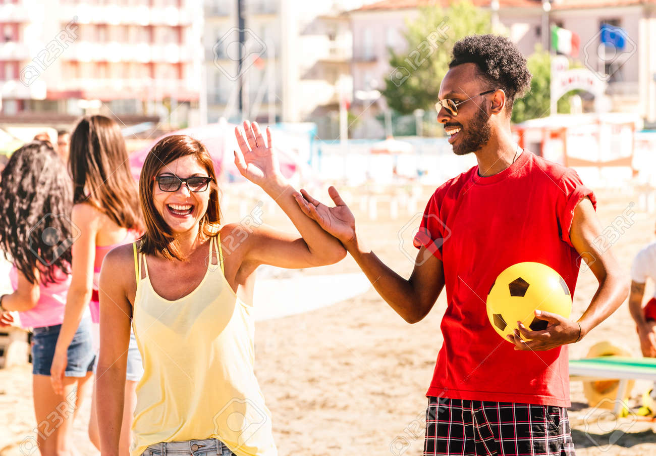 Multiracial couple ready to play beach soccer on sunny day - Summer vacation concept and multi cultural friendship with guy and girl having fun together - Bright warm filter with focus on right man - 166116858