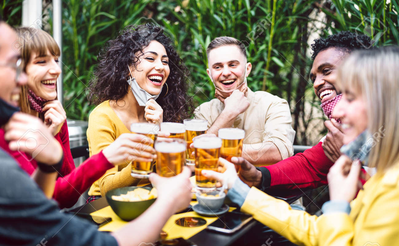 Young people toasting beer wearing open face mask - 166540804
