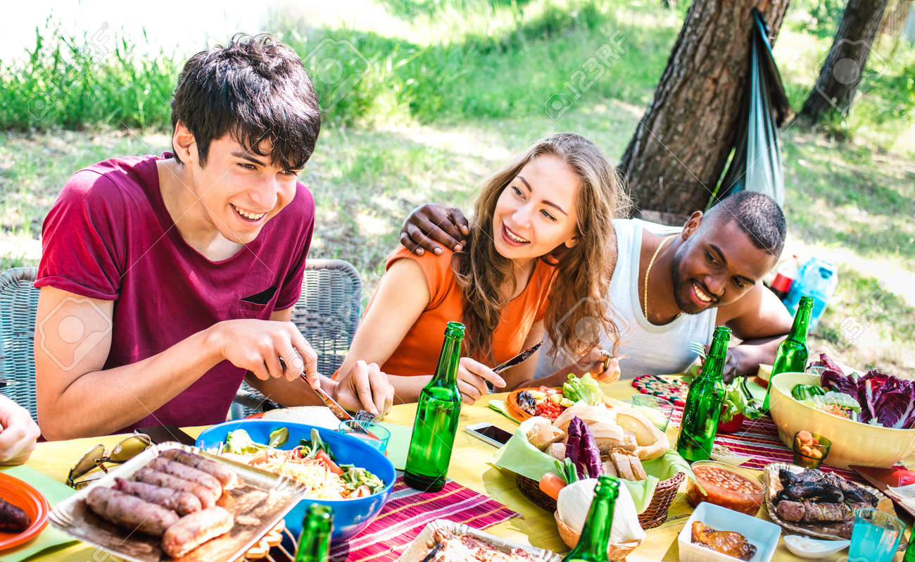 Happy people having fun together at barbecue picnic party - Young multiracial friends at pic nic social gathering - Youth life style concept with guys and girls eating at barbeque - Warm bright filter - 166975454