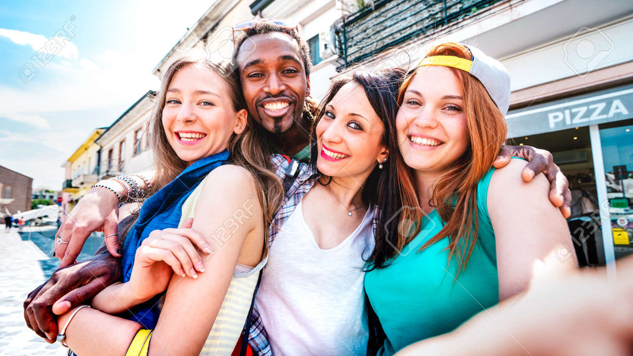 Multicultural tourists group taking selfie at old town tour - Happy millenial life style concept with young people having fun around city after lockdown reopen - Bright vivid filter with focus on face - 166975936