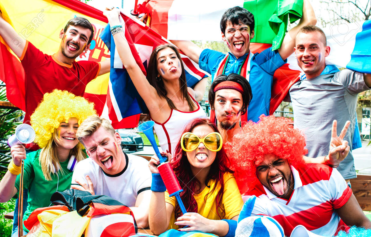 Young football supporter fans cheering with international flags at soccer match - Happy people with multicolored tshirts having fun together outdoors - Sport championship concept on warm vivid filter - 166975989
