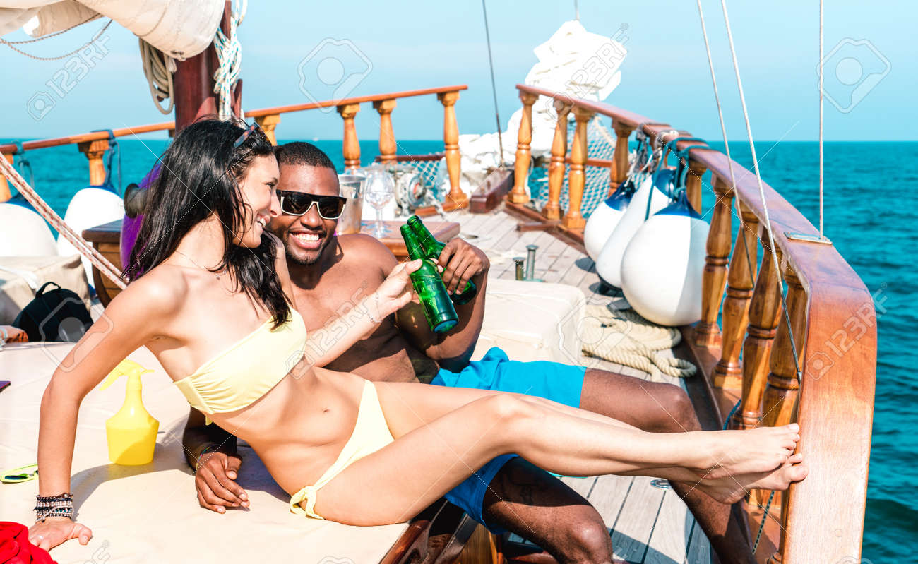 Young couple in love on sailing boat cheering with beer bottles - Happy girlfriend and boyfriend making party at cruise travel on luxury sailboat - Bright vivid filter with focus on faces - 166975873
