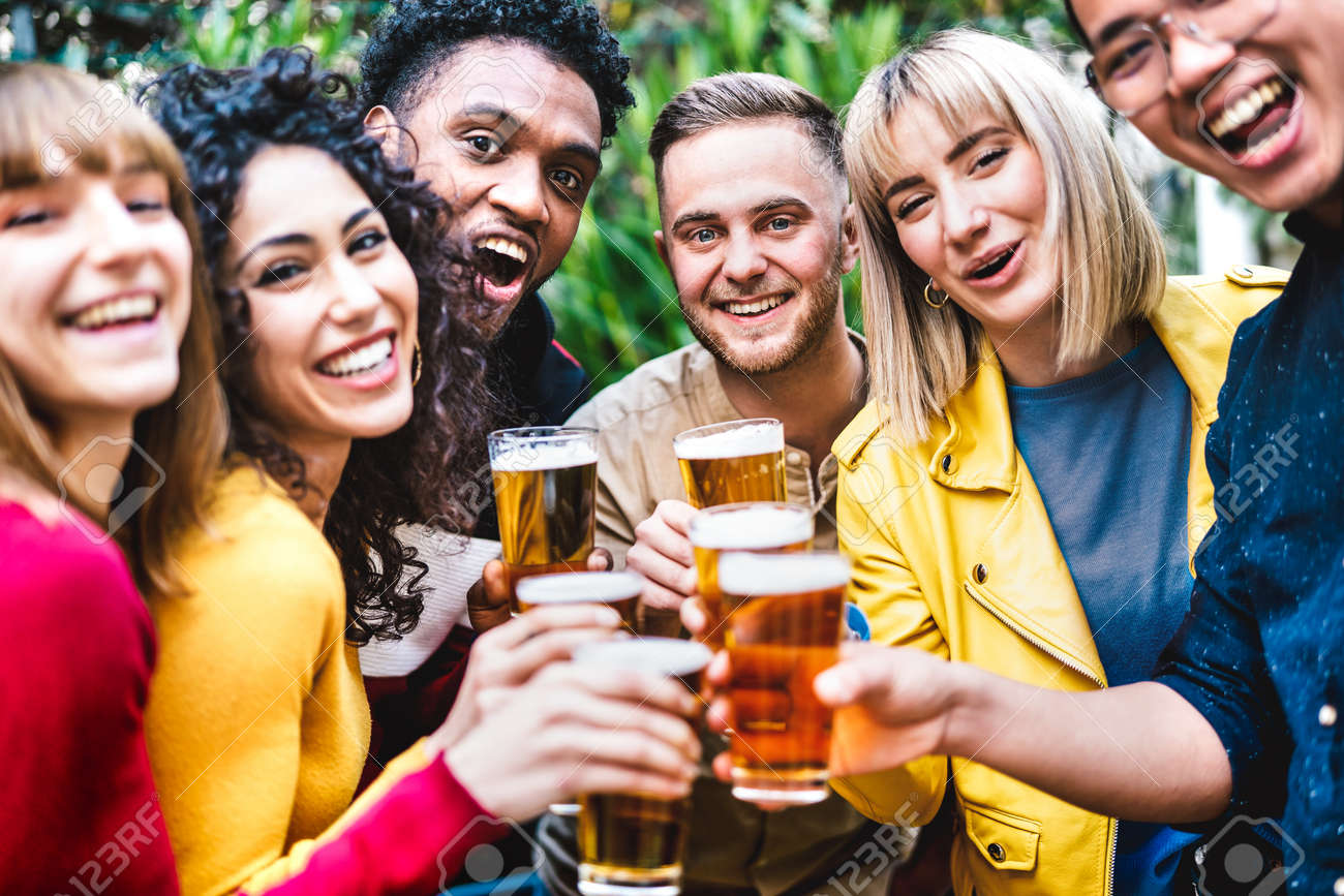 Happy friends toasting beer at brewery bar dehor - Friendship life style concept with young millennial people enjoying time together at open air pub - Warm vivid filter with focus on central guy - 168285654