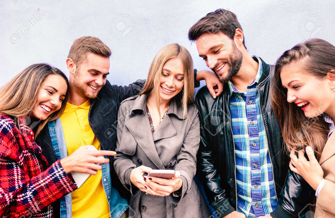 Milenial friends on fun moment using mobile smart phone - Young people always connected at social media devices - Technology concept with modern teenagers sharing content online - Bright vivid filter - 168285666