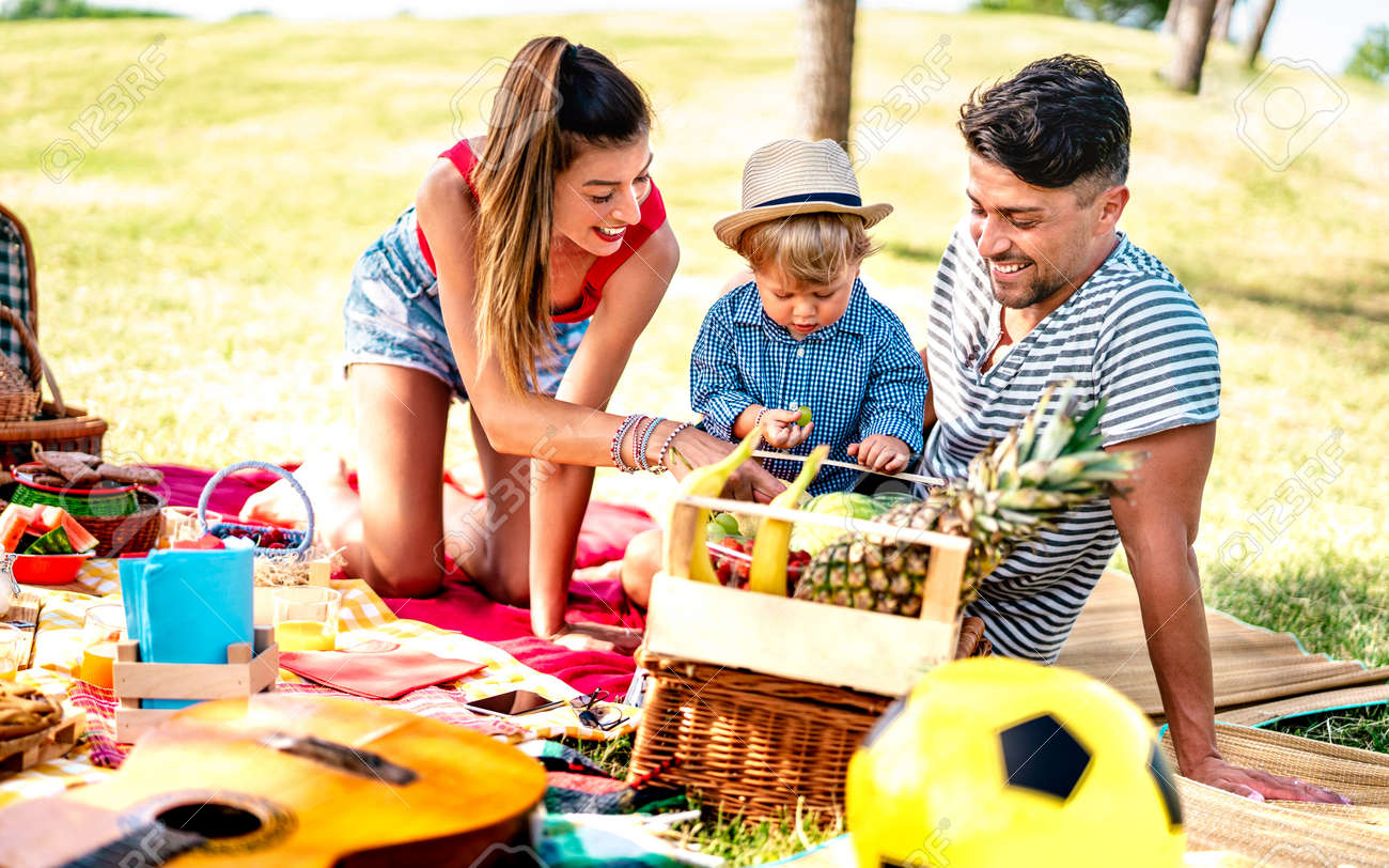 Happy family having fun together at picnic party - Joy and love life style concept with mother and father playing with child at park - Warm bright filter with focus on faces - 169667492