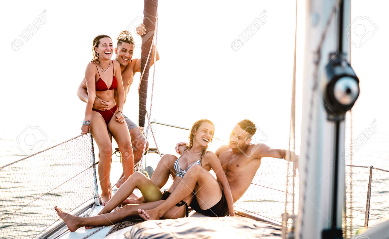 Young couple friends chilling on sailboat at sea ocean trip - Guys and girls having summer fun together at sail boat party day - Luxury concept on warm bright filter - 169667503
