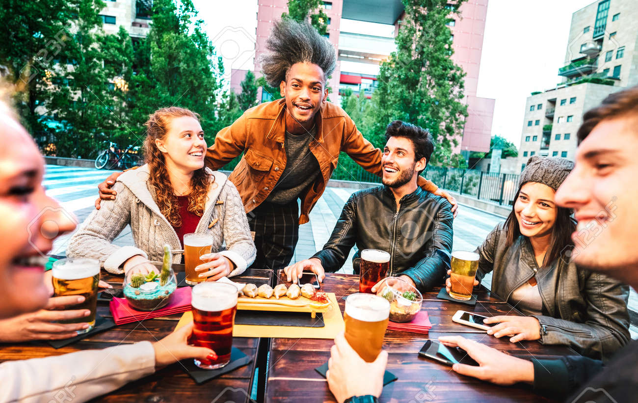 Young people drinking beer at brewery bar dehor - Friendship lifestyle concept with multicultural friends spending happy hour time together at open air pub garden - Warm bright filter - 170441018