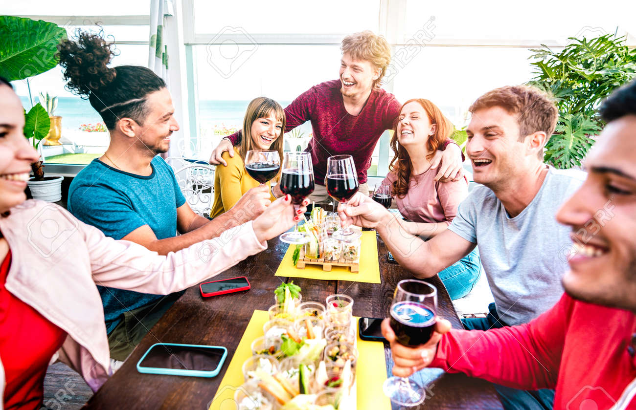 Happy millenial people having fun together drinking wine at terrace on private house party - Young friends eating finger food at restaurant reopening - 170440962