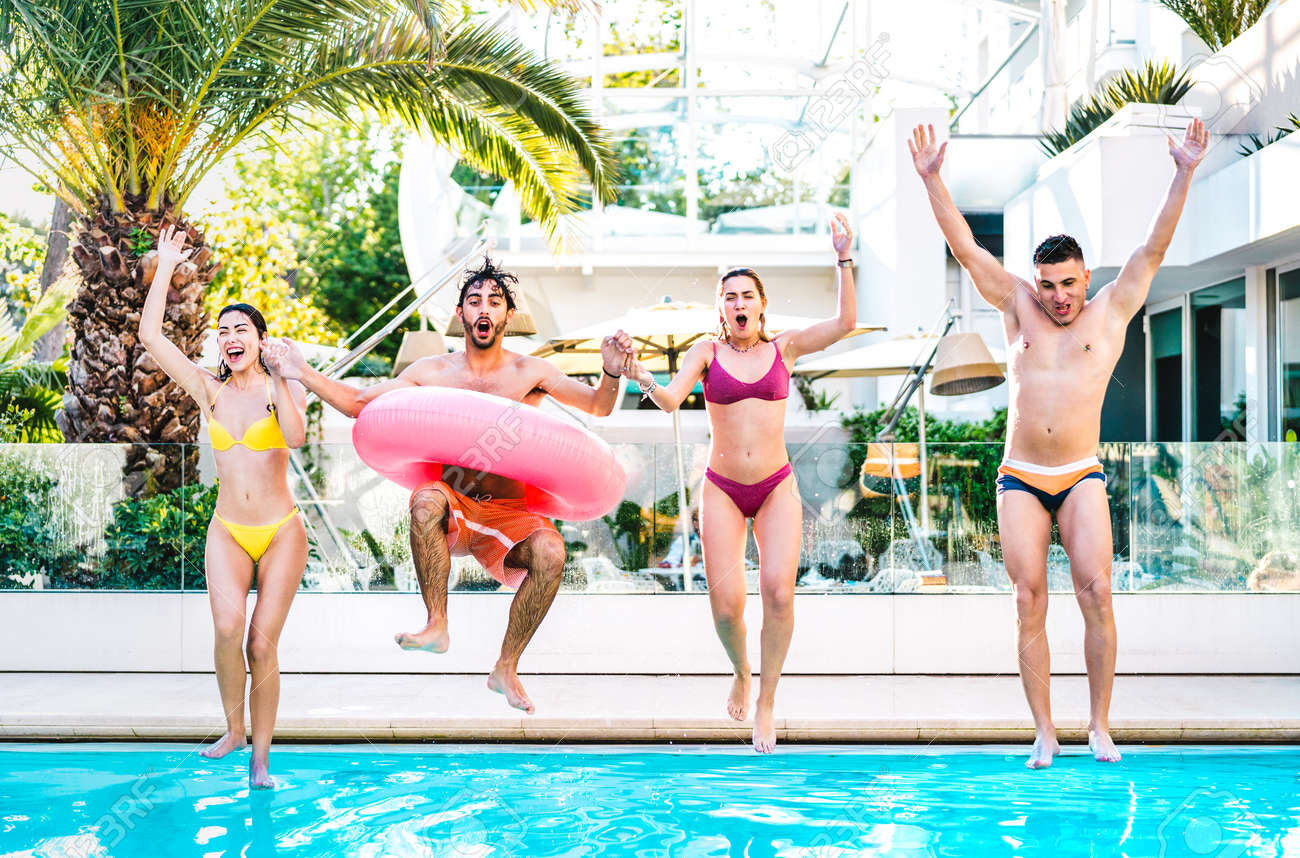 Front view of friends jumping in swimming pool with lilo airbed at luxury resort party - Life style vacation concept with happy guys and girls having fun games in summer day - 170931965