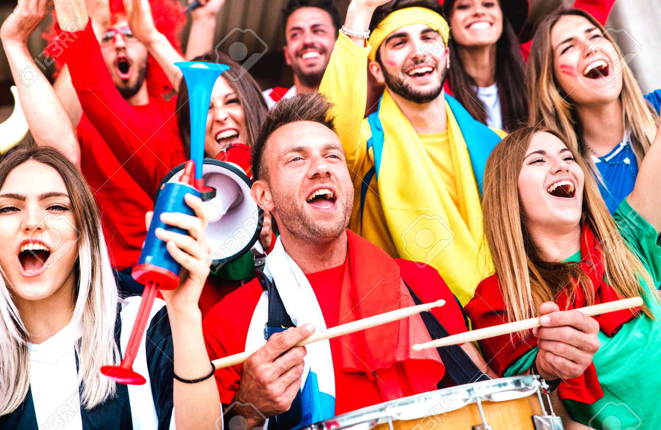 Football supporter fans cheering with drums watching soccer cup match at stadium bleachers - Young people group with multicolored t-shirt having excited fun on sport championship - 170441374
