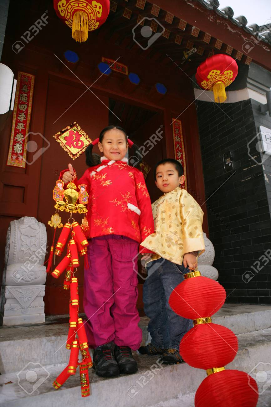Two children(5-12 years) standing in front of chinese traditional house door smiling Stock Photo - 23325460