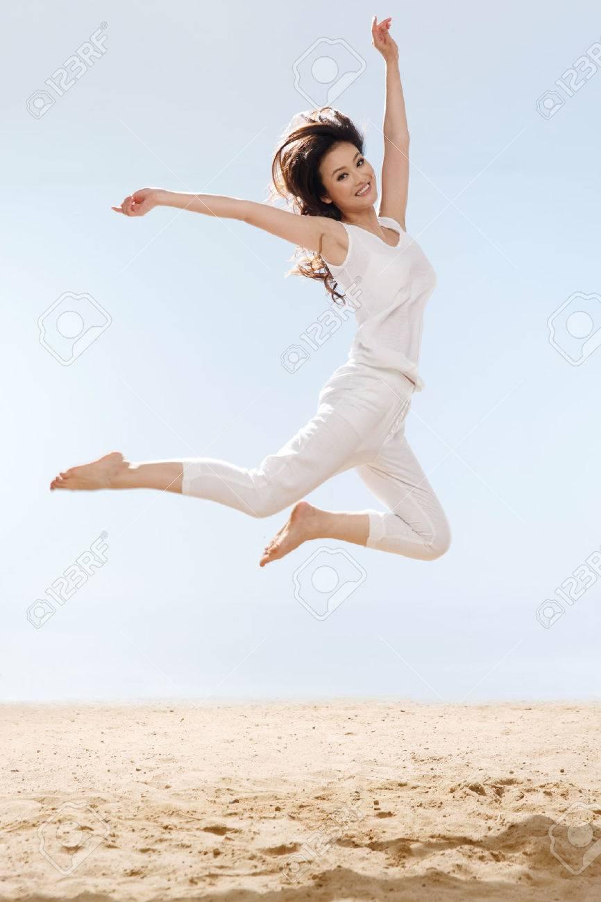 Woman jumping on beach Stock Photo - 34917221