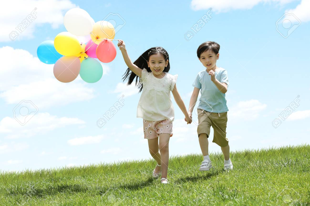 Happy children play on the grass - 98592116