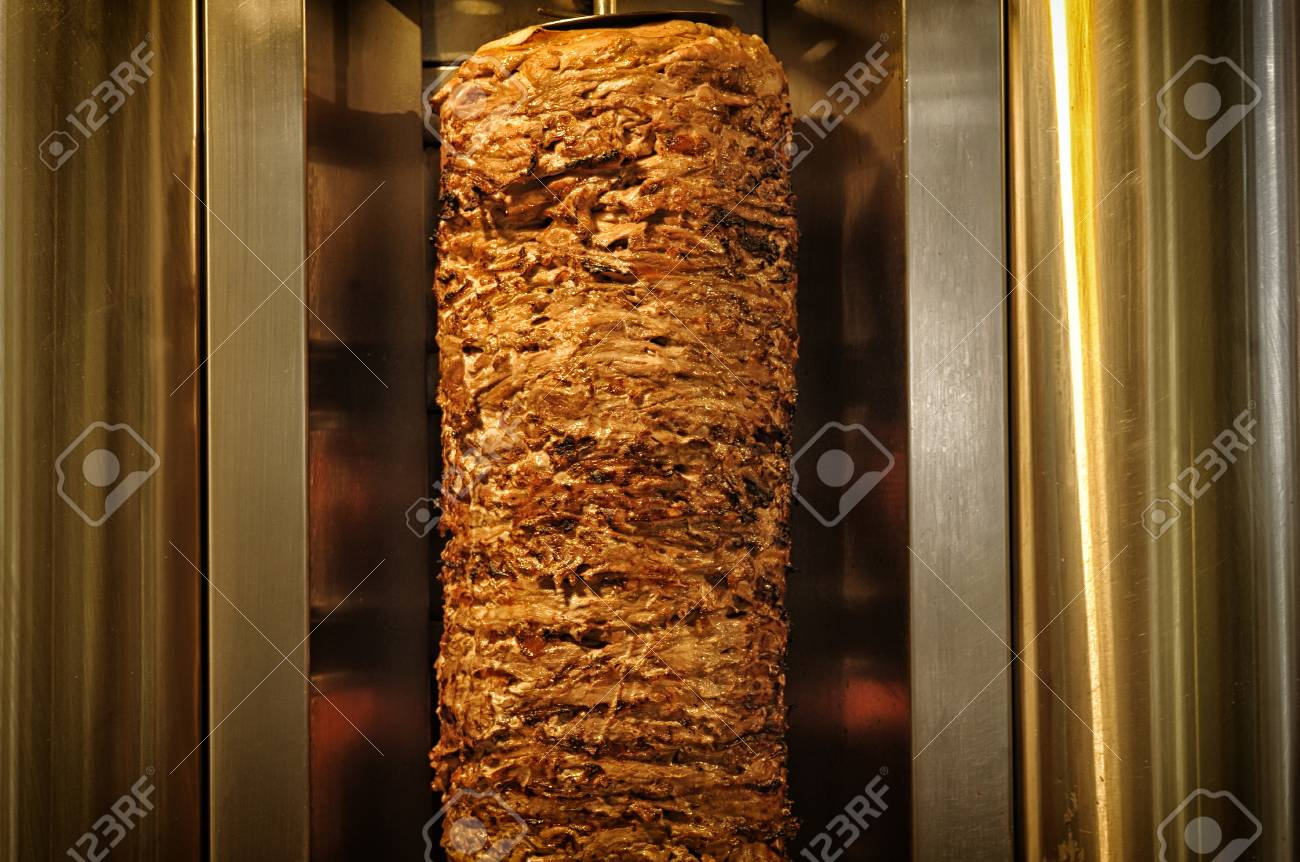 A stick of Arab shwarma in front of the grill, a popular Middle