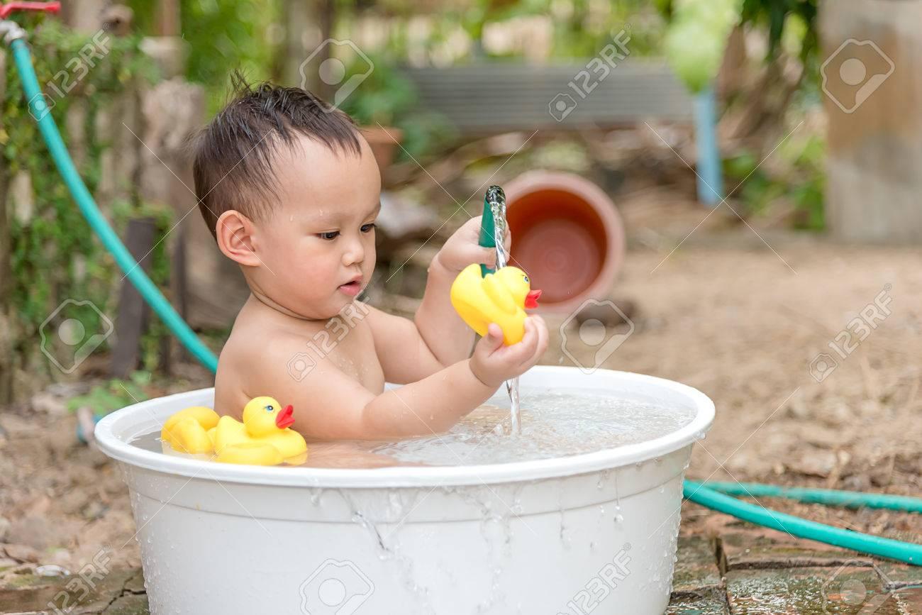 Vasca Da Bagno Neonato : Neonato asiatico bagno esterno nella vasca da bagno bianco. egli è