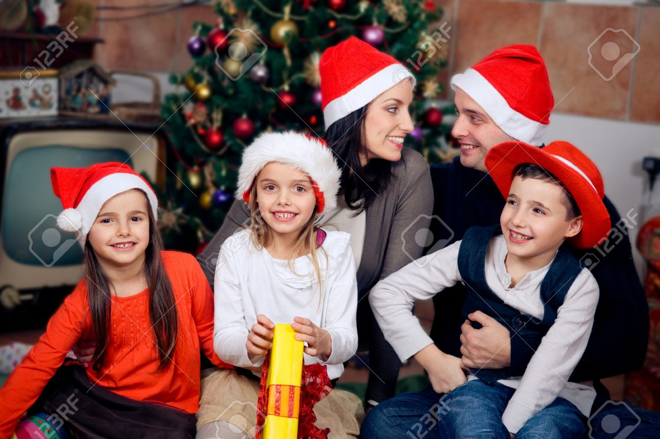 Family Around Christmas Tree Part - 37: Happy Family Sitting In Front Of Christmas Tree Celebrating Christmas Stock  Photo - 16891415