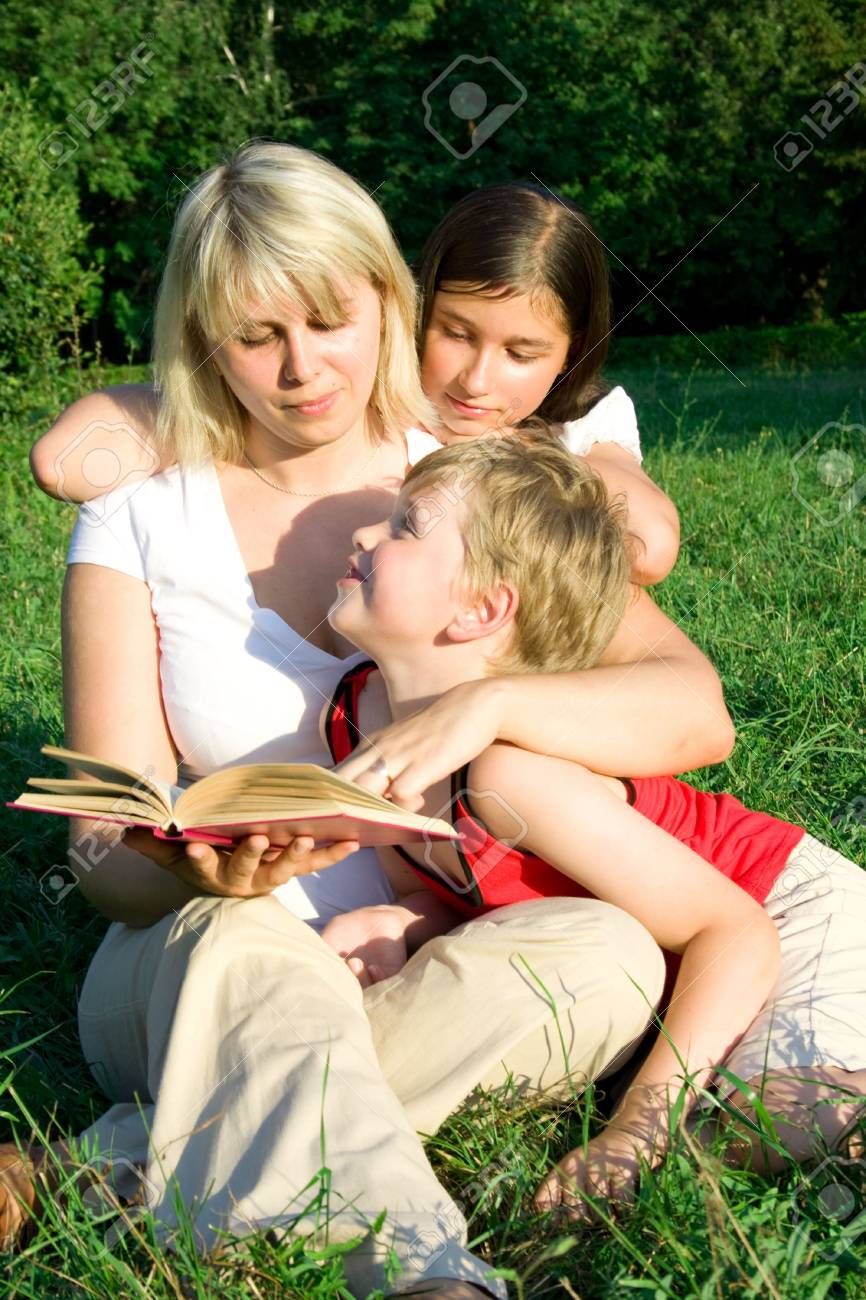 The young woman sits on a grass and reads the book to the children Stock Photo - 3343194