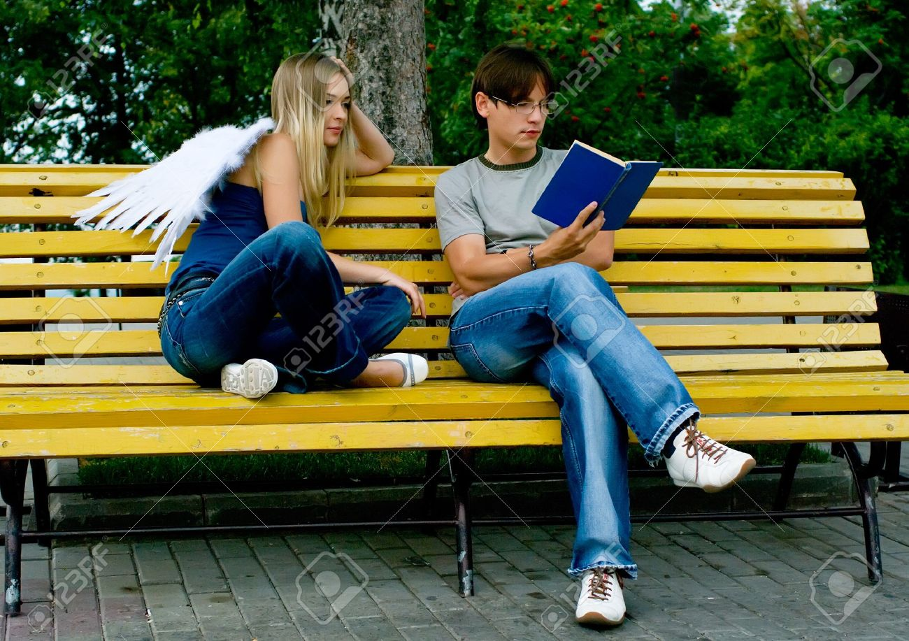 A Young Men Reading A Book In A Summer Park. Guardian Angel Is ...