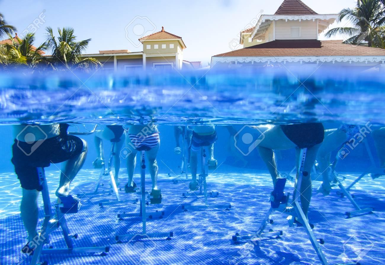Fitness class doing aqua aerobics on exercise bikes in swimming..