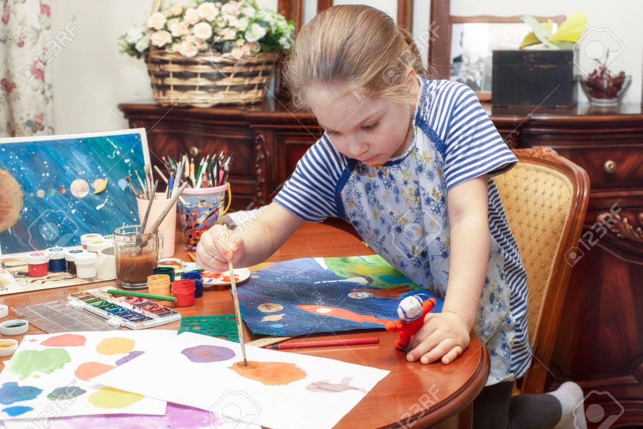 A child paints a papier mache astronaut figurine with a brush - 168750244
