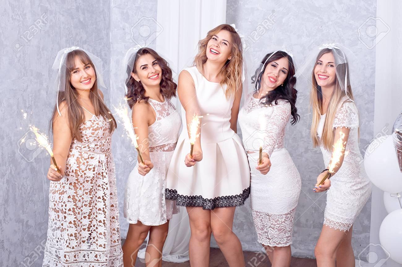 43f3702799 Cinco mujeres jóvenes con estilo felices en elegantes vestidos blancos de  pie en una fila riendo