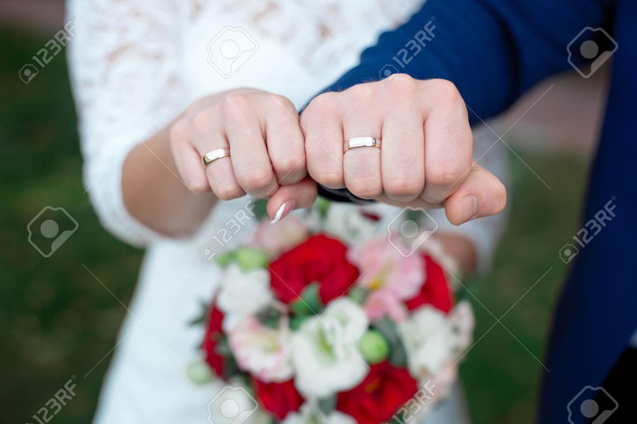 Close-up Bride and grooms hands with wedding rings - 100151661