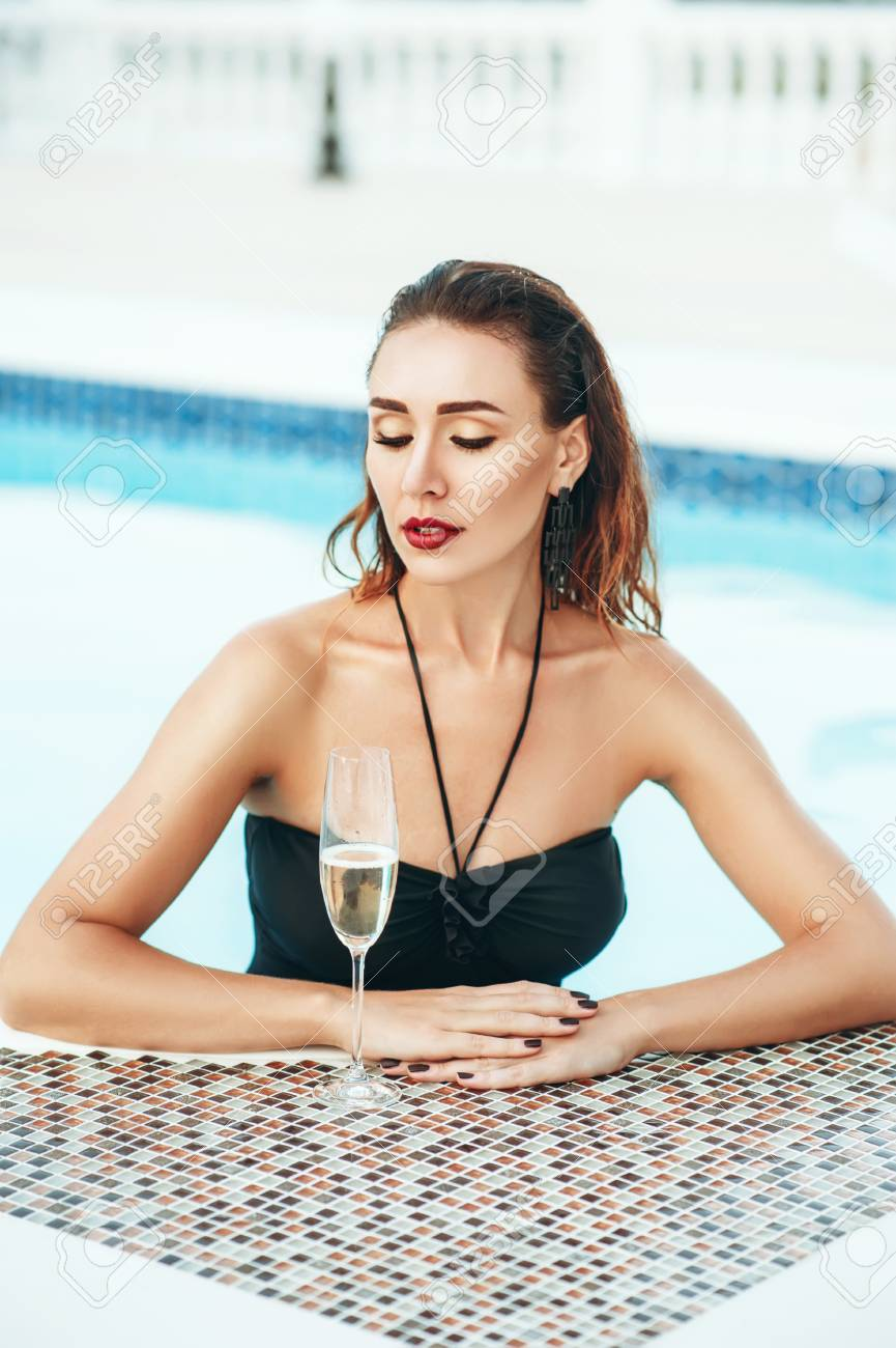 6f0a99980c1d7 Elegant sexy woman in black bikini on the perfect body is posing near a swimming  pool with wineglass champagne in private villa. Sexuality beauty.