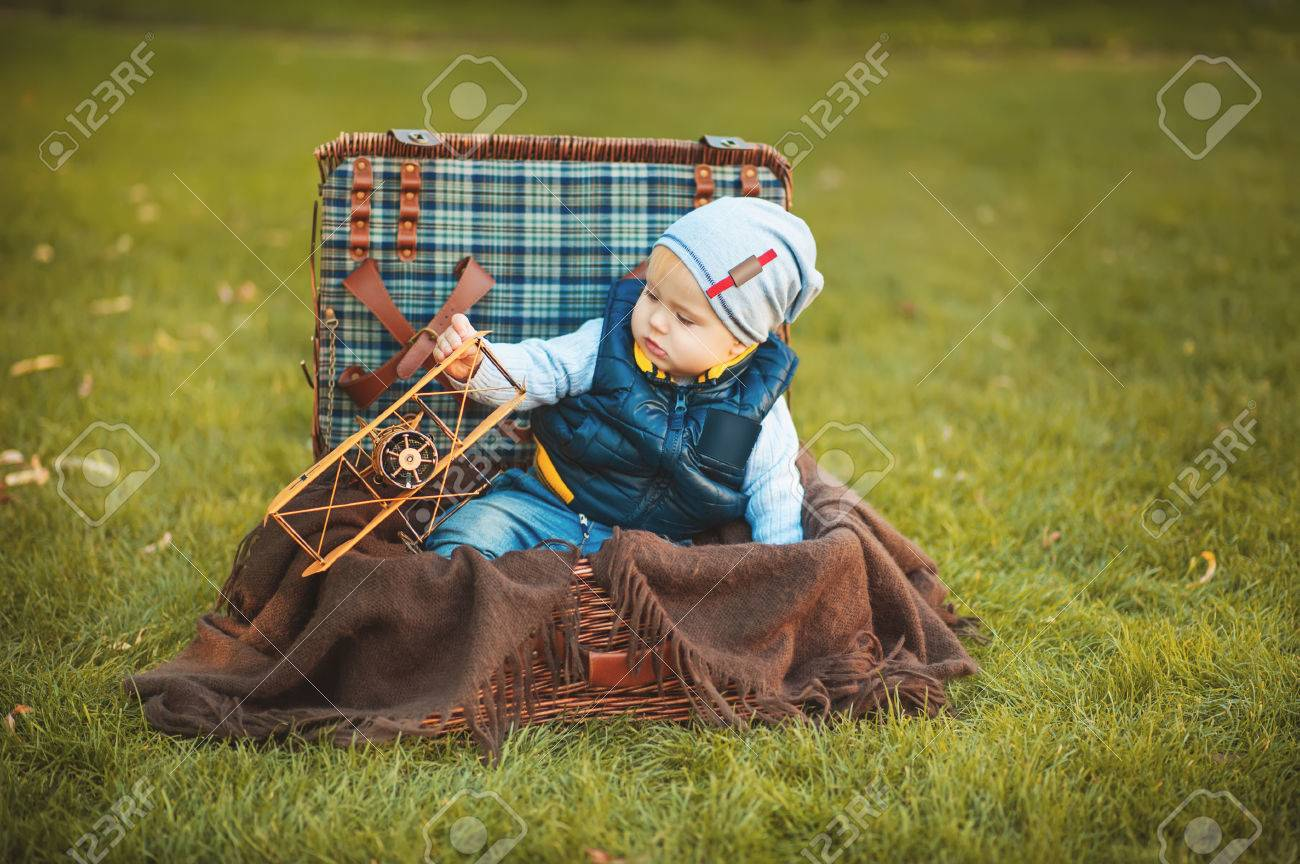 Happy little boy playing with airplane toy while sitting in suitcase on green autumn lawn. Children enjoying activity outdoor. Childhood, baby, holiday, people, hobby concepts. Foto de archivo - 87475920