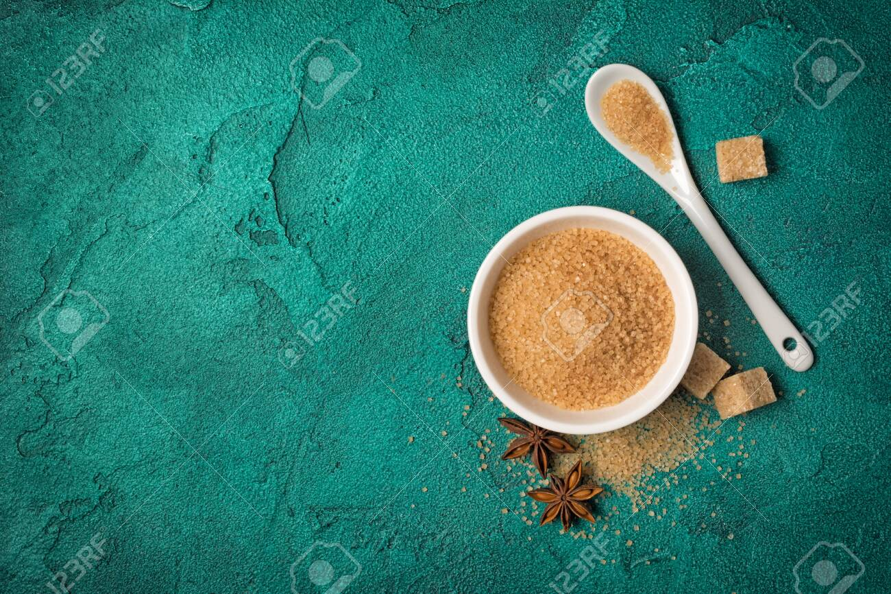 Top view of brown cane granulated sugar in white bowl with spices for confectionery on green concrete background with copy space - 121994447