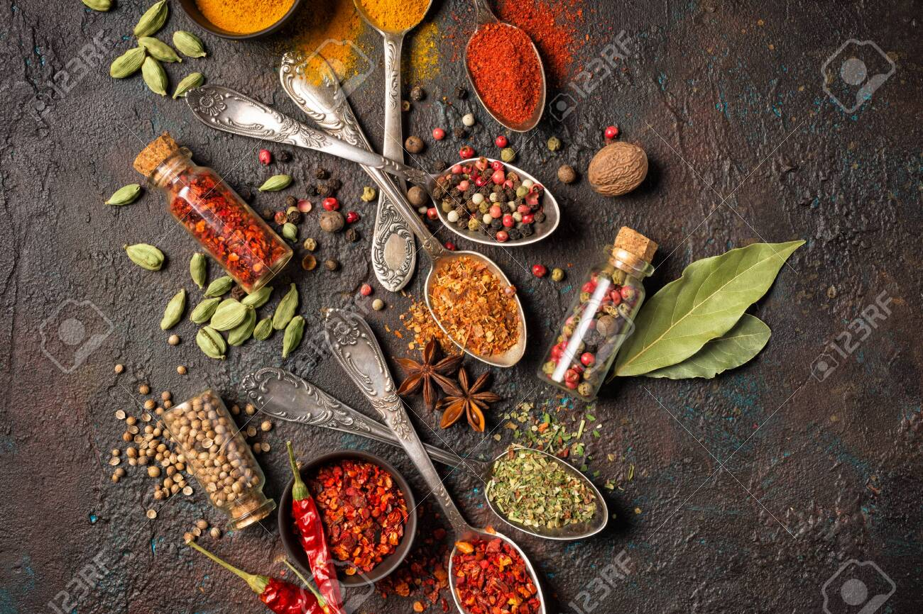 Top view of mix bright spices in vintage silver spoons, bowls and vials as ingredient for healthy food on brown grunge background - 143482525