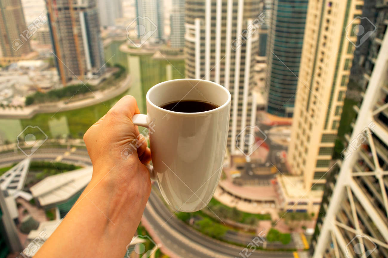 Female hand holds big white cup of morning coffee with city skyscrapers view of modern city Dubai. Coffee cup on city background. - 168934751
