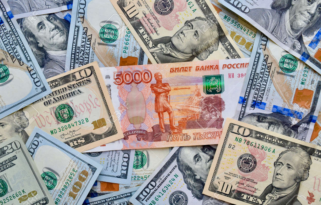 Russian national currency on top of US dollar banknote, top view of mixed rouble banknotes. Russian and American paper money. Rubles and US dollars exchange rate. - 168933088