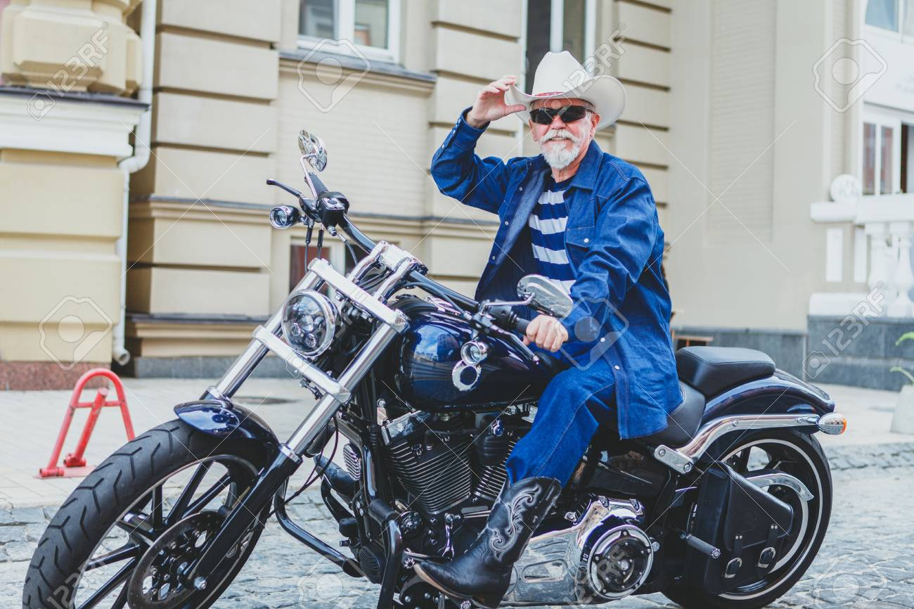 An Elderly Man In A Cowboy Hat Is Sitting On A Motorcycle. A.. Stock ... 2ced7de111f