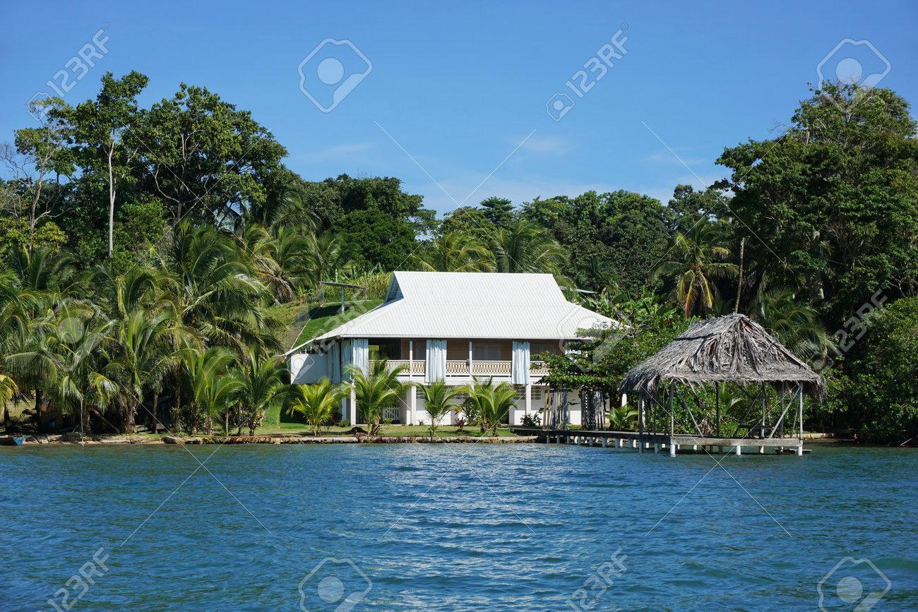 propiedad frente al mar con una casa caribe y choza de paja sobre el mar