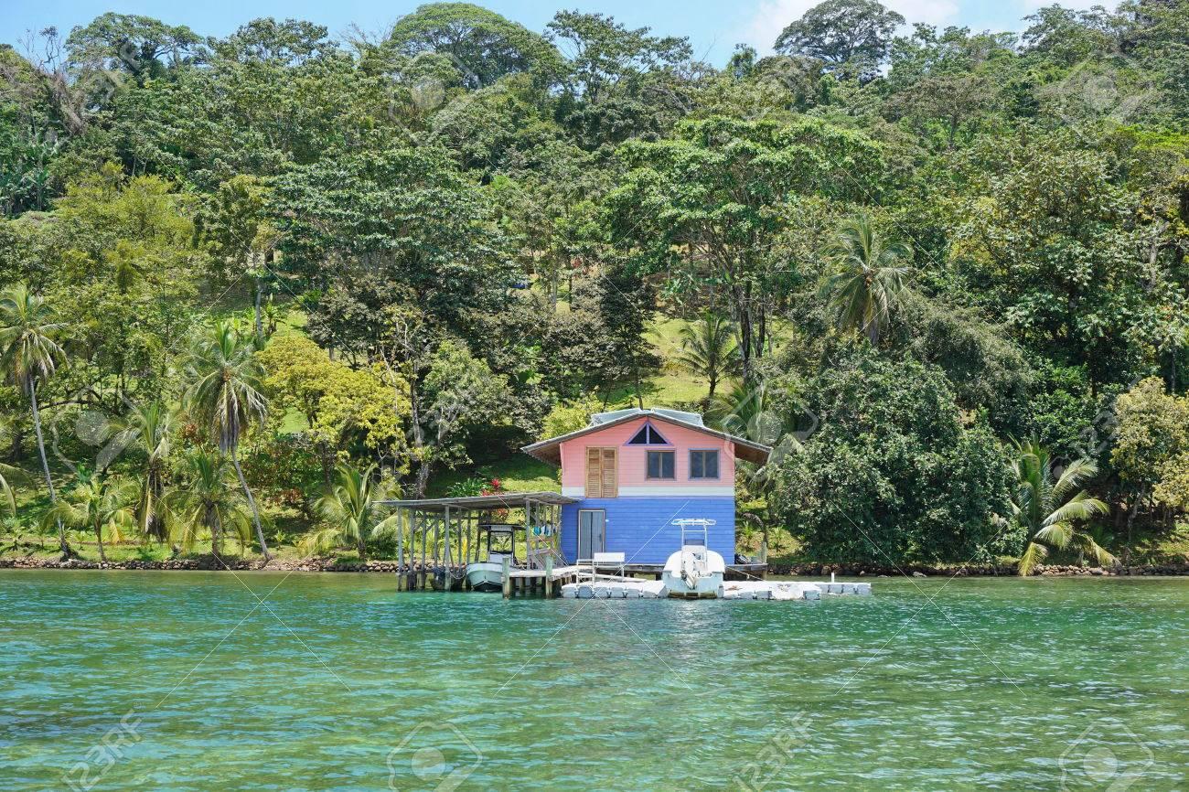casa sobre el mar con los barcos en el muelle y una exuberante vegetacin tropical en