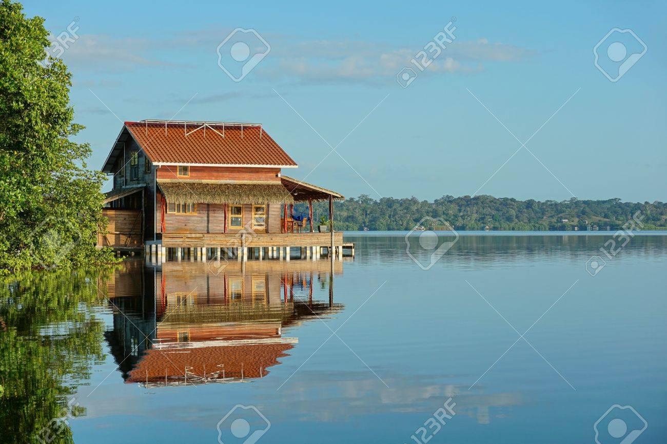 foto de archivo casa de madera tropical sobre pilotes en el agua tranquila en una baha archipilago de bocas del toro del mar caribe amrica central