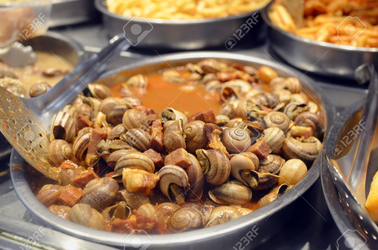 Edible snails stewed in wine sauce with vegetables and bacon,