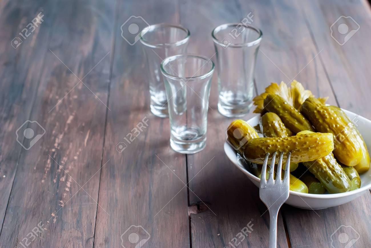 Petit verre à vin de vodka russe et snack de concombre de sel sur la table en bois. copie espace