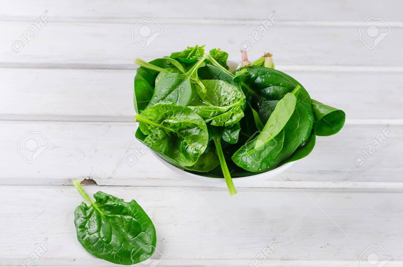 raw green spinach leaves in white bowl on wooden old rustic white table, copy space - 121182876