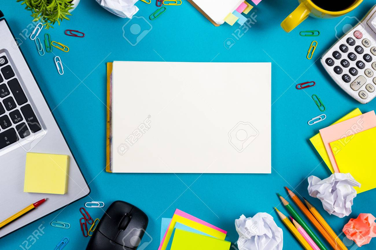 Office table desk with set of colorful supplies, white blank note pad, cup, pen, pc, crumpled paper, flower on blue background. Top view and copy space for text. - 54297126