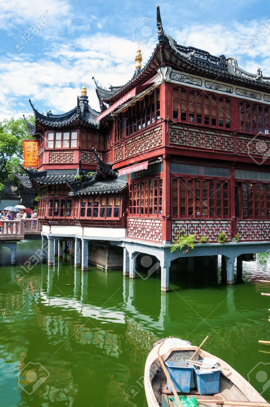 Une maison de thé traditionnelle chinoise repose sur des piliers au-dessus  d\'un petit étang au Jardin Yuyuan à Shanghai, en Chine