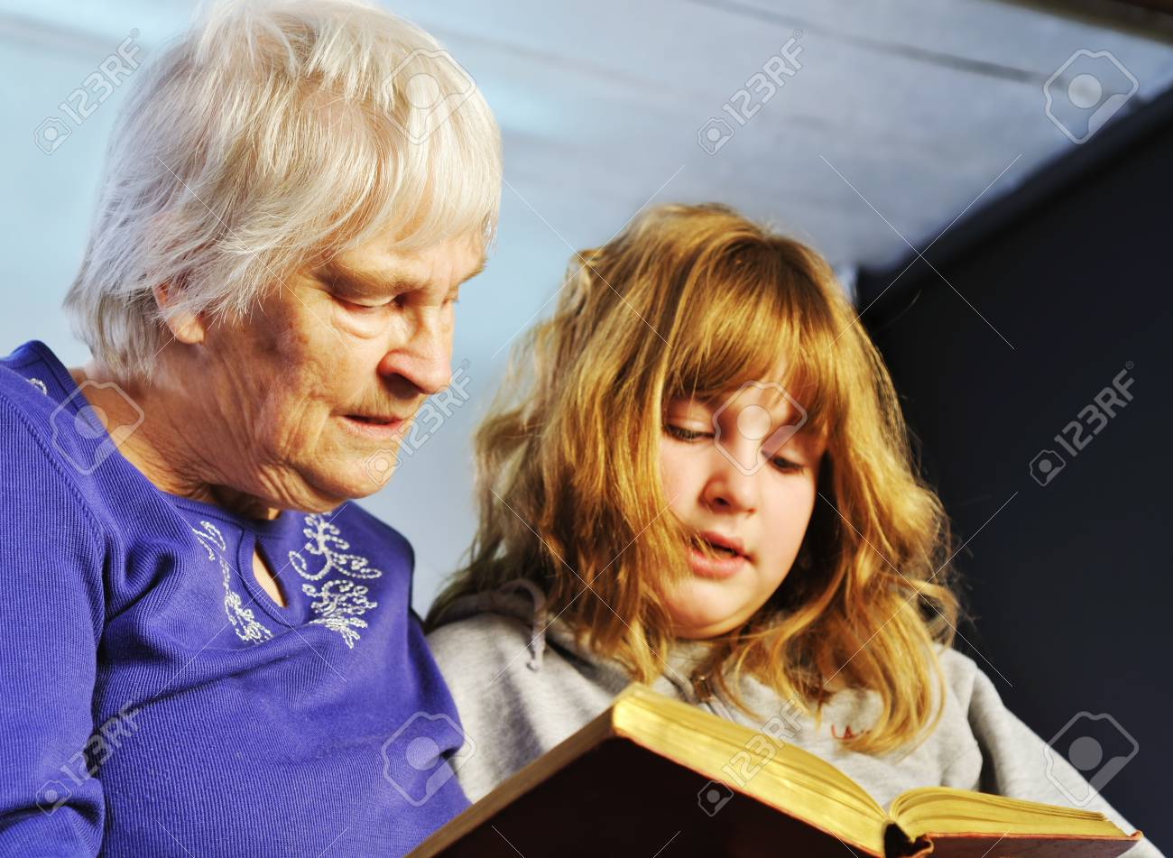 teenage girl and senior woman reading a book together Stock Photo - 13621194