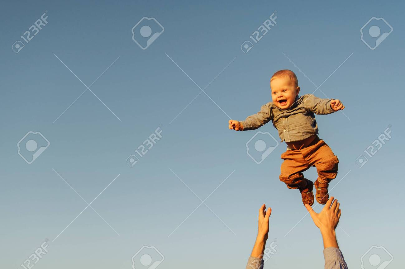 Happy baby boy because his father is throwing him up to the sky. Background of the sky - 148215384